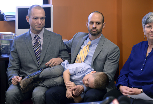Al Hartmann  |  The Salt Lake Tribune Plaintiffs Matthew Barraza, left, and Tony Milner, who are legally married, listen to the announcement with their napping son Jesse of ACLU of Utah filing of a lawsuit Tuesday Jan. 21, 2014, in Salt Lake City over Utah's refusal to recognize valid same-sex marriages that occurred before the U.S. Supreme Court issued a stay.