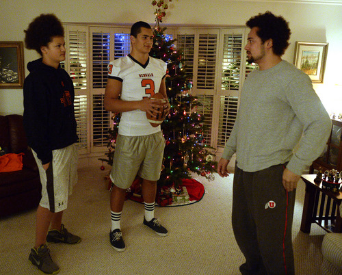Rick Egan  | The Salt Lake Tribune   Salua Masina (left) and Loi Masina (right) chat with their brother, Brighton High football star, Osa Masina, while visiting their grandparents home in Salt Lake City Wednesday, December 18, 2013