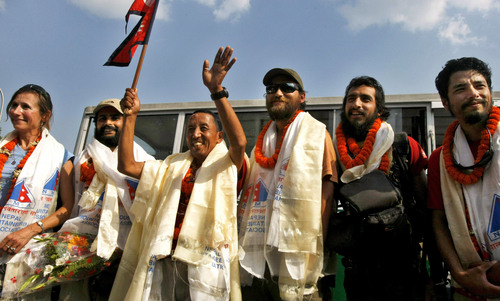 "(AP Photo/Binod Joshi) Apa Sherpa, who has scaled Everest a record 21 times, waves to the media with members of his team after their expedition, named ""The Great Himalaya Trail"" as they return at the airport in Katmandu, Nepal, Sunday, April 22, 2012. The trek covered 1,700 kilometers (1,050 miles) in 88 days."