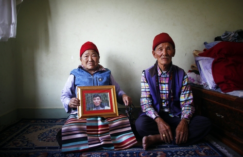 (AP Photo/Niranjan Shrestha) Nimdige Sherpa holds a portrait of her son, Ang Kaji Sherpa, who was killed in an avalanche on Mount Everest. Her husband, Ankchu Sherpa, is seated beside her in their rented apartment in Katmandu, Nepal, on Wednesday, April 23, 2014. Dozens of Sherpa guides packed up their tents and left Mount Everest's base camp Wednesday, after the avalanche deaths of 16 of their colleagues exposed an undercurrent of resentment by Sherpas over their pay, treatment and benefits.