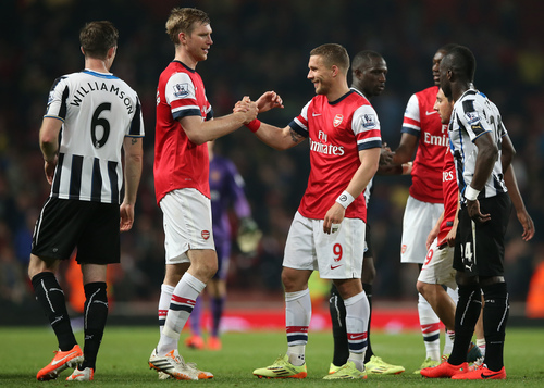 Arsenal's Per Mertesacker, second left, goes to hug teammate Lukas Podolski, center right, following the end of the English Premier League soccer match between Arsenal and Newcastle United at the Emirates stadium in London, Monday, April  28,  2014. Arsenal won the game 3-0. (AP Photo/Alastair Grant)