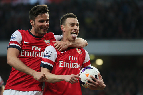 Arsenal's Laurent Koscielny, right, celebrates with teammate Oliver Giroud after scoring the opening goal during their English Premier League soccer match between Arsenal and Newcastle United at the Emirates stadium in London, Monday, April 28,  2014. (AP Photo/Alastair Grant)