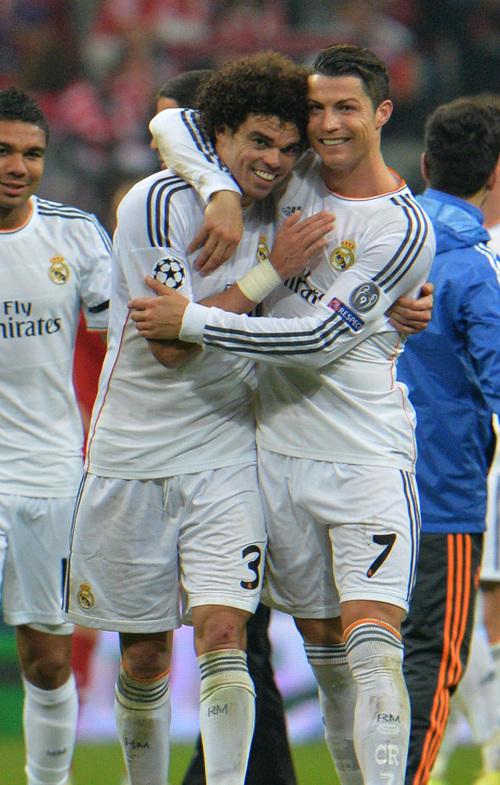 Real's Cristiano Ronaldo, right, and Pepe celebrate after winning the Champions League semifinal second leg soccer match between Bayern Munich and Real Madrid at the Allianz Arena in Munich, southern Germany, Tuesday, April 29, 2014. (AP Photo/Kerstin Joensson)