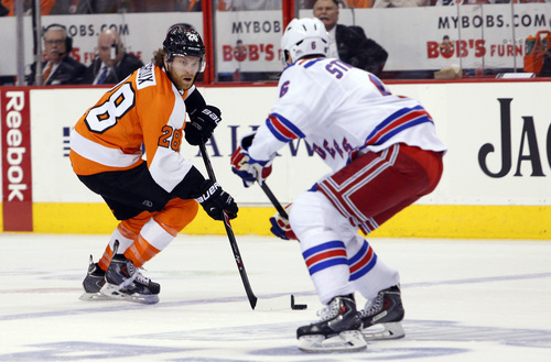 Philadelphia Flyers' Claude Giroux, left, skates the puck into the zone with New York Rangers' Anton Stralman, right, of Sweden, during the first period in Game 6 of an NHL hockey first-round playoff series, Tuesday, April 29, 2014, in Philadelphia. (AP Photo/Chris Szagola)