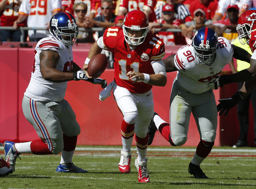 Kansas City Chiefs quarterback Alex Smith (11) scrambles away from New York Giants defensive tackle Cullen Jenkins (99) and defensive end Jason Pierre-Paul (90) during the first half of an NFL football game at Arrowhead Stadium in Kansas City, Mo., Sunday, Sept. 29, 2013. (AP Photo/Orlin Wagner)