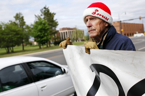 Protester John Walters of Oklahoma City holds a sign urging Gov. Mary Fallin to issue a stay in the execution of two inmates, near the Governor's Mansion in Oklahoma City on Tuesday, April 29, 2014. A botched execution that used a new drug combination left an Oklahoma inmate writhing and clenching his teeth on the gurney Tuesday, leading prison officials to halt the proceedings before the inmate's eventual death from a heart attack. (AP Photo/The Oklahoman, KT King)