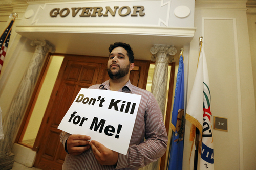 Hossein Dabiri with Oklahoma Coalition Against the Death Penalty holds a sign protesting the death penalty at the State Capitol in Oklahoma City, Tuesday April 29, 2014. Oklahoma prison officials halted the execution of an inmate after the delivery of a new three-drug combination on Tuesday failed to go as planned. (AP Photo/The Oklahoman, Steve Gooch)