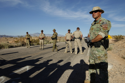 Federal law enforcement officers block a road at the Lake Mead National Recreation Area near Overton, Nev. Thursday, April 10, 2014. In the foreground are the shadows of protestors. Two people were detained while protesting the roundup of cattle owned by Cliven Bundy on the road. (AP Photo/Las Vegas Review-Journal, John Locher)
