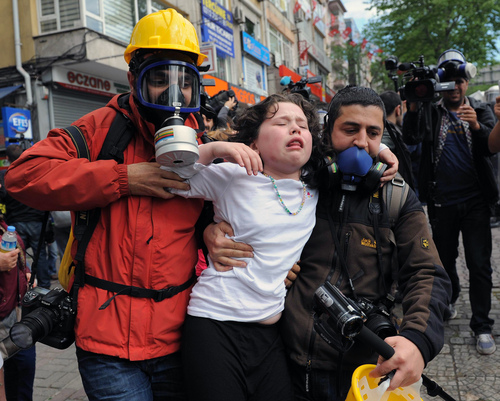People help a child affected by teargas as riot police use water cannons and teargas to disperse thousands of people trying to reach the city's main Taksim Square to celebrate May Day in Istanbul, Turkey, Thursday, May 1, 2014. Clashes erupted between May Day demonstrators and riot police as crowds determined to defy a government ban tried to march to the city's iconic Taksim Square. Security forces pushed back demonstrators with water cannons and tear gas. (AP Photo/Emrah Gurel)