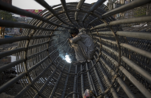 A Pakistani worker fixes steel for a construction of a bridge in Rawalpindi, Pakistan, Thursday, May 1, 2014. Nation-wide rallies have been organized in Pakistan to mark May Day. Participants of the rallies demanded implementation of labor laws and better wages. (AP Photo/B.K. Bangash)