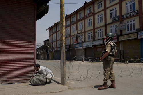 A Kashmiri man bends to get past a barbwire checkpoint in front an Indian paramilitary soldier in Srinagar, India, Thursday, May 1, 2014. Parts of Indian-controlled Kashmir remained under curfew Thursday, while general strikes were being staged in other areas after government forces fatally shot a man during an anti-India protest. (AP Photo/Bernat Armangue)