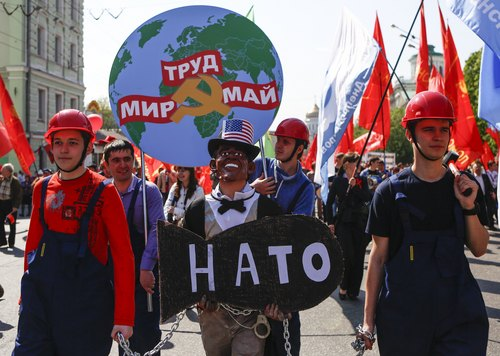 People in helmets (left and right), dressed as Russian factories workers, hold a man wearing Barack Obama's mask with mock NATO's bomb in chains, as they take part in a Communists demonstration in downtown Moscow, Russia, Thursday, May, 1, 2014. Thousands of Communists, members of Russia's main political parties and opposition activists staged competing marches in Moscow and other cities Thursday marking the traditional May Day holiday. Poster at the background reads : Peace, Labour, May. (AP Photo/Denis Tyrin)