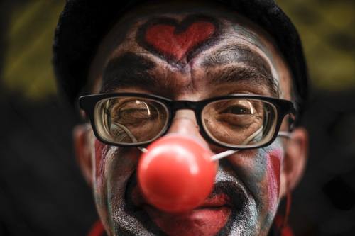Paco Fiallo, 39 years old, looks at the camera of a photographer as he earns a living on the street with his face painted as a clown during May Day, in Pamplona northern Spain, Thursday, May 1, 2014. Tens of thousands of workers marked May Day in European cities with a mix of anger and gloom over austerity measures imposed by leaders trying to contain the eurozone's intractable debt crisis.(AP Photo/Alvaro Barrientos)
