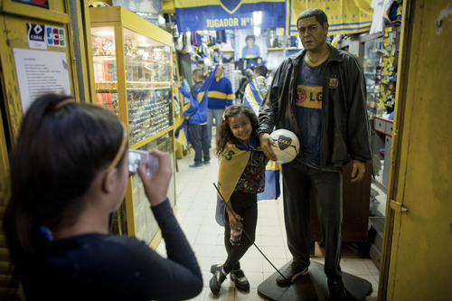 """A young Boca Juniors' fan poses for a photo next to a statue of midfielder Juan Roman Riquelme during a demonstration in Buenos Aires, Argentina, Thursday, May 1, 2014. Thousands of fans gathered outside the Alberto J. Armando stadium, better known as """"La Bombonera,"""" to demand the club to renew Riquelme's contract. (AP Photo/Victor R. Caivano)"""