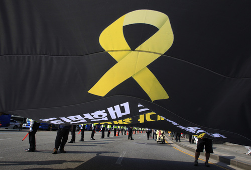 Workers carry a flag depicting a yellow ribbon as a sign of hope for the safe return of missing passengers of the sunken ferry Sewol during a May Day rally to pay tribute to the victims of the  accident in Seoul, South Korea, Thursday, May 1, 2014. An off-duty captain of the sunken South Korean ferry has told investigators that the owners ignored his warning that the ship shouldn't carry too much cargo because it wasn't very stable, a prosecutor said Wednesday. (AP Photo/Ahn Young-joon)