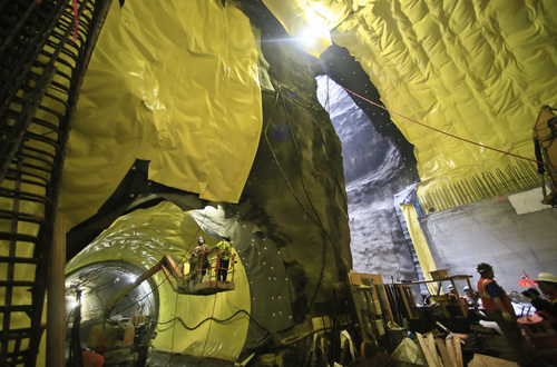 Construction workers install waterproofing material during construction inside the cavern of the Second Avenue subway tunnel at 86th Street, Thursday May 1, 2014 in New York.  The $4.45 billion project to extend the Q line up and down Second Avenue in Manhattan is expected to be ready for riders by the end of 2016.  (AP Photo/Bebeto Matthews)