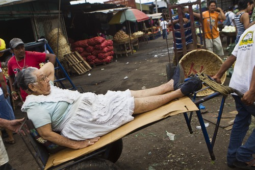 """Vendor Carmen Diaz, 83, is transported on a cart to her post at the Oriental Market in Managua, Nicaragua, Thursday, May 1, 2014. Known as """"Chanita,"""" Diaz has worked since she was 8-years-old at the market, where she sells a hodgepodge of household items that include small piggy banks, coat hooks and liquid cleaners. Diaz suffers from a herniated disc in her spine, so for the past two years she has arrived at her stall on a cart usually used for transporting market goods, but lined with cardboard for her comfort. (AP Photo/Esteban Felix)"""