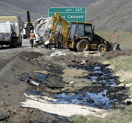 Al Hartmann  |  The Salt Lake Tribune UDOT crews create berms and absorb crude oil from an oil tanker truck that crashed and spilled oil on westbound I-80 near the Lambs Canyon exit in Parley's Canyon Wednesday April 30, 2014. Some oil seeped into a storm drain before it was contained..