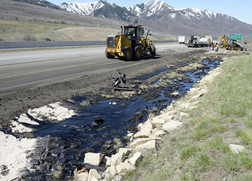 Al Hartmann  |  The Salt Lake Tribune UDOT crews create berms and absorb crude oil from oil tanker truck the crashed and spilled oil on westbound I-80 near the Lambs Canyon exit in Parley's Canyon Wednesday April 30.  Some oil seeped into a storm drain before it was contained.
