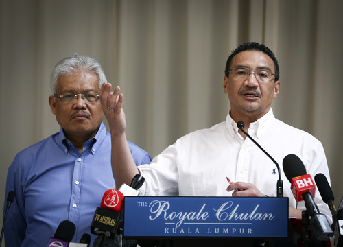 FILE- In this April 19, 2014 file photo, Malaysian Deputy Minister of Foreign Affairs Hamzah Zainudin, left, listens as Malaysia's acting Transport Minister Hishammuddin Hussein answers a question from a journalist during a press conference on the missing Malaysia Airlines Flight 370 at a hotel in Kuala Lumpur, Malaysia. Air traffic controllers did not realize that Malaysia Airlines Flight 370 was missing until 17 minutes after it disappeared from civilian radar, according to the preliminary report on the plane's disappearance released Thursday, May 1, 2014, by Malaysia's government. (AP Photo/Vincent Thian, File)