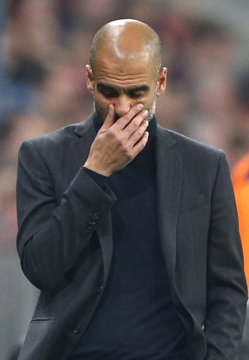 Bayern head coach Pep Guardiola touches his face during the Champions League semifinal second leg soccer match between Bayern Munich and Real Madrid at the Allianz Arena in Munich, southern Germany, Tuesday, April 29, 2014. (AP Photo/Matthias Schrader)