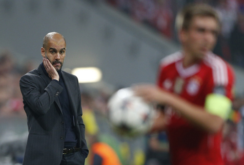 Bayern head coach Pep Guardiola, left, looks to team captain Philipp Lahm during the Champions League semifinal second leg soccer match between Bayern Munich and Real Madrid at the Allianz Arena in Munich, southern Germany, Tuesday, April 29, 2014. (AP Photo/Matthias Schrader)