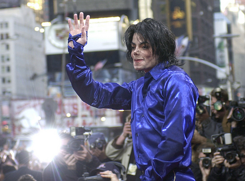 """FILE - Nov. 7, 2001 file photo, Michael Jackson waves to crowds gathered to see him at his first ever in-store appearance to celebrate his new album """"Invincible"""" in New York's Times Square.When Michael Jackson's record label released his first posthumous album a year after he passed in 2010, producer Rodney Jerkins was asked to work on the project and he declined. Years later, the hitmaker, who worked heavily on Jackson's 2001 comeback album """"Invincible,"""" says he now feels comfortable producing Jackson music after the King of Pop suddenly died in 2009. He produced the title track from the upcoming album, """"Xscape,"""" out May 13, 2014.  (AP Photo/Suzanne Plunkett, file)"""