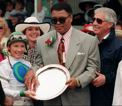 Former heavyweight champion and Louisville native, Muhammad Ali presents the trophy to jockey Donna Barton, left, and trainer D. Wayne Lukas, right, after Lost Pan won the second race at Churchill Downs Saturday, May 6, 1995, in Louisville, Ky.   (AP Photo/Michelle Wood)