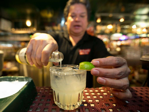 In this Monday, April 28, 2014 photo, bartender Mario Sanchez crafts a margarita cocktail at the bar of El Coyote, a Mexican restaurant in Los Angeles. Thousands of restaurateurs from coast to coast who have fallen victim to the Great Green Citrus Crisis of 2014. The lime has skyrocketed in price in recent weeks, quadrupling or, in some areas, going even higher. (AP Photo)