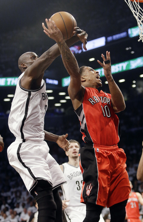 Brooklyn Nets' Kevin Garnett, left, knocks the ball away from Toronto Raptors' DeMar DeRozan (10) during the first half of Game 6 of the opening-round NBA basketball playoff series Friday, May 2, 2014, in New York. (AP Photo/Frank Franklin II)