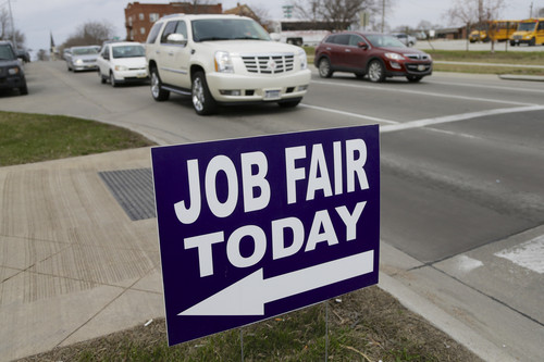 In this April 10, 2014, photo, a sign points to a job fair on the campus of Kaplan University in Lincoln, Neb.  At first glance, April's U.S. employment report suggested that the agonizingly slow 5½-year-old economic recovery has gained new momentum. Yet several cautionary signs emerged from the report. (AP Photo/Nati Harnik)