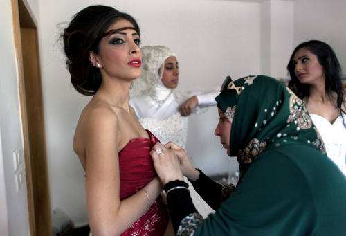 In this photo taken Thursday, May 1, 2014, a model backstage is prepared to display a creation by designer Fayzeh Pearl ahead the opening day of the Palestine Fashion Week 2014, in the West Bank city of Ramallah.  While Ramallah is not internationally known for fashion, organizers hope that its Palestinian Fashion Week will draw more attention to local designers. (AP Photo/Nasser Nasser)