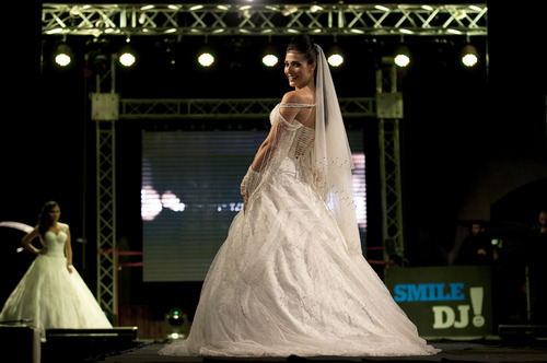 In this photo taken Friday, May 2, 2014, a model displays a creation by designer Fayzeh Pearl during the Palestine Fashion Week 2014, in the West Bank city of Ramallah. Pearl showed off more traditional designs, including beaded wedding dresses and colorful formal attire. (AP Photo/Nasser Nasser)