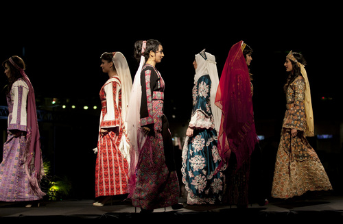 "In this photo taken Thursday, May 1, 2014, models display embroidered  creations by designer Intisar Abdo during the opening day of the Palestine Fashion Week 2014, in the West Bank city of Ramallah. Tamer Halabi, an organizer of the event, said the show in part shows that ""we Palestinians exist,"" and ""we are surviving, we have talents, we have designers, and we can compete with world fashion houses."" (AP Photo/Nasser Nasser)"