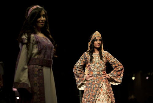 In this photo taken Thursday, May 1, 2014, two models display a blend of traditional Palestinian embroidery and modern designs in a creation by designer Intisar Abdo during the opening day of the Palestine Fashion Week 2014, in the West Bank city of Ramallah. The three-day show, which ended Saturday, May 3, 2014, saw models prowl the catwalk in the only major fashion show in the Palestinian territories. (AP Photo/Nasser Nasser)