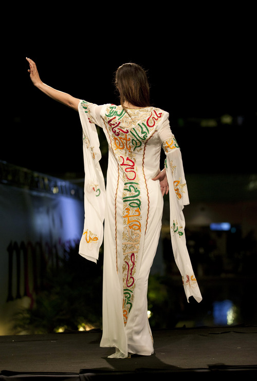 "In this photo taken Friday, May 2, 2014, a model displays a creation with embroidered Arabic calligraphy by Jordanian-Palestinian designer Intisar Abdo during the second day of the Palestine Fashion Week 2014, in the West Bank city of Ramallah. Tamer Halabi, an organizer of the event, said the show in part shows that ""we Palestinians exist."" and ""We are surviving, we have talents, we have designers, and we can compete with world fashion houses.""  (AP Photo/Nasser Nasser)"
