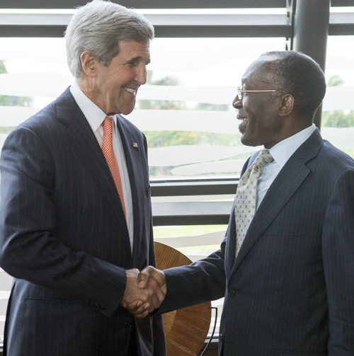 Democratic Republic of Congo Foreign Minister Raymond Tshibanda, right, shakes hands with US Secretary of State John Kerry upon arrival at N'djili Airport in Kinshasa, Democratic Republic of Congo, Saturday, May 3, 2014. (AP Photo/Saul Loeb, pool)