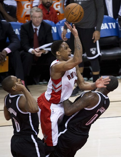 Toronto Raptors guard DeMar DeRozan, center, is charged with an offensive foul against Brooklyn Nets forward Andray Blatche as Nets forward Alan Anderson, left, looks on during the second half of Game 7 of the opening-round NBA basketball playoff series in Toronto, Sunday, May 4, 2014. (AP Photo/The Canadian Press, Nathan Denette)