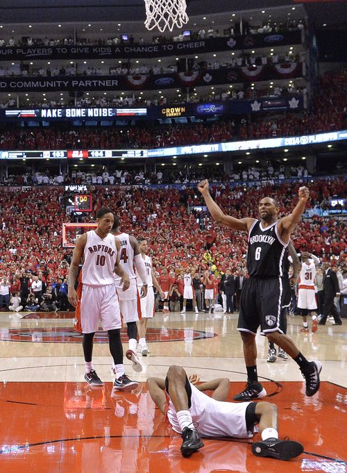 Brooklyn Nets forward Alan Anderson (6) celebrates as Toronto Raptors guard Kyle Lowry, front center, lays on the ground after missing the basket following second half NBA game seven playoff basketball action in Toronto on Sunday, May 4, 2014.The Nets defeated the Raptors to advance to the next round. (AP Photo/The Canadian Press, Nathan Denette)