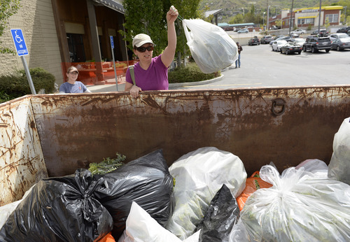 """Rick Egan     The Salt Lake Tribune  Lynette Thorn tosses in a bag of myrtle spurge, as part of the plant exchange program at REI, during the 8th annual """"Purge Your Spurge"""" event, Saturday, May 3, 2014.  There were also cleanups at Dimple Dell Park and the Bonneville Shoreline Trail at the base of Grandeur Peak."""