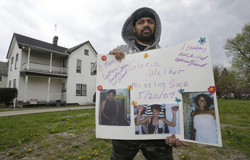 In this Saturday, May 3, 2014 photo, Manuel Walker holds up a poster of his mother, Gloria, in the neighborhood where she went missing in 2007 in Cleveland. Gloria lived in the second floor apartment on the left. What hasn't changed since the stunning discovery of the three women held captive by Ariel Castro is that others are still missing from the same streets. The list of missing people in Cleveland makes up about one out of every 10 cases in the entire state. (AP Photo/Tony Dejak)
