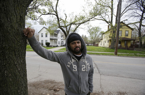 In this Saturday, May 3, 2014 photo, Manuel Walker stands near the home, left, where his mother once lived in Cleveland. Gloria Walker went missing in 2007. What hasn't changed since the stunning discovery of the three women held captive by Ariel Castro is that others are still missing from the same streets. The list of missing people in Cleveland makes up about one out of every 10 cases in the entire state. (AP Photo/Tony Dejak)