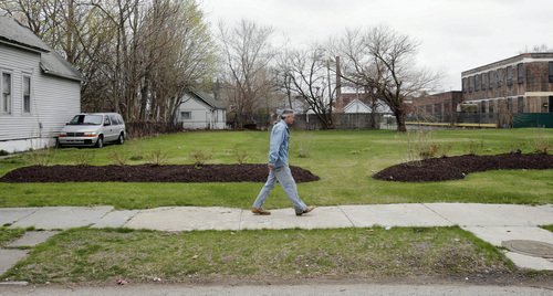 In this April 23, 2014 photo, a man walks past an empty lot, which once was the home of Ariel Castro in Cleveland. The home was fortified with boarded-up windows and makeshift alarms where Castro held three women captive for nearly a decade. (AP Photo/Tony Dejak)
