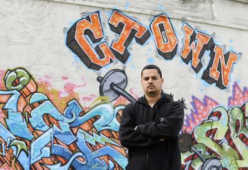 This Monday, April 28, 2014, photo shows Angel Arroyo standing in front of a graffiti covered wall in Cleveland. Arroyo and the father of Gina DeJesus, who was freed in May 2013 after 10 years of captivity by Ariel Castro, went to door-to-door last summer after a young woman went missing in a neighboring city. Finding DeJesus, Amanda Berry and Michelle Knight generated new tips other girls who disappeared years ago in the same area. (AP Photo/Mark Duncan)