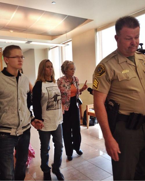 The mother of Jesse Horowitz, center, walks out of a court hearing Monday, May 5, 2014, surrounded by supporters and court bailiffs. Horowitz, 17, was killed in a stabbing in April 2014. Larry Beach, 20, is charged with first-degree felony murder and second-degree felony obstruction of justice.  Photo by Marissa Lang