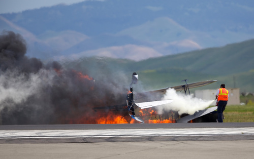 A worker fights a fire after a vintage biplane crashed upside-down on a runway at an air show at Travis Air Force Base in Fairfield, Calif., Sunday, May 4, 2014. The pilot, Edward Andreini, 77, of Half Moon Bay, was killed when the plane, flying low over the tarmac, crashed and caught fire. (AP Photo/Bryan Stokes)