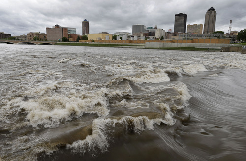 """FILE - In this May 30, 2013, file photo, water splashes over the Center Street Dam in the swollen Des Moines River in downtown Des Moines, Iowa.  Climate change's assorted harms """"are expected to become increasingly disruptive across the nation throughout this century and beyond,"""" the National Climate Assessment concluded Tuesday. (AP Photo/Charlie Neibergall, File)"""