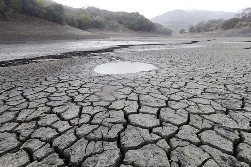 FILE - This Feb. 7, 2014, file photo shows the cracked-dry bed of the Almaden Reservoir in San Jose, Calif.   Global warming is rapidly turning America the beautiful into America the stormy, sneezy and dangerous, according to a new federal scientific report. And those shining seas? Rising and costly, the report says.  (AP Photo/Marcio Jose Sanchez, File)