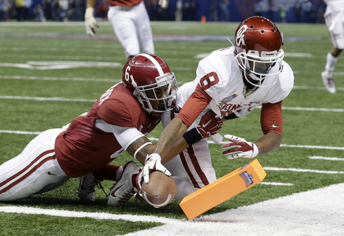 Oklahoma wide receiver Jalen Saunders (8) scores a touchdown as Alabama defensive back Ha Ha Clinton-Dix (6) tries to tackle during the first half of the Sugar Bowl NCAA college football game in New Orleans, Thursday, Jan. 2, 2014. (AP Photo/Rusty Costanza)