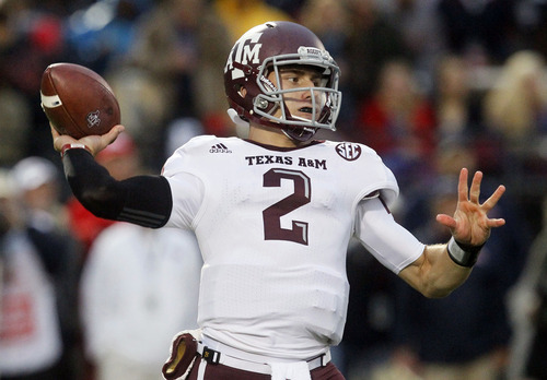 FILE - In this Oct. 6, 2012, file photo, Texas A&M quarterback Johnny Manziel throws a short pass in the first quarter of an NCAA college football game against Mississippi in Oxford, Miss. Manziel could become the first freshman to win the Heisman Trophy when the award is presented on Saturday night.(AP Photo/Rogelio V. Solis, File)